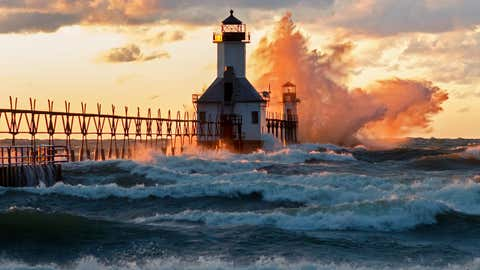 Twenty foot waves pound the outer lighthouse and create a 60 to 70 foot high splash of water which is illuminated by the setting sun. (Tom Gill)