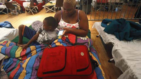 Brandy Battle, of Davant, La., sits on a cot with her son Patrick Bell, 5, on her 27th birthday and the anniversary of Hurricane Katrina, at an evacuation shelter after Isaac made landfall as a hurricane, in Belle Chasse, La., Wednesday, Aug. 29, 2012.