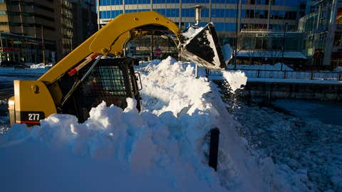 A worker using a skid steer loader dumps snow into the Chesapeake Bay a day after Winter Storm Jonas dropped nearly 30 inches of snow in Baltimore, Maryland on Sunday, January 24, 2016. (Shawn Hubbard/weather.com)