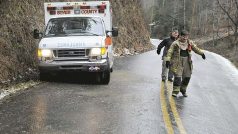 Caton's Chapel volunteer firefighters Charles Power, left, and Devin Keeler slide their way past a stranded ambulance on Henrytown Road in Sevier County, Tenn., Friday, Jan. 25, 2013.