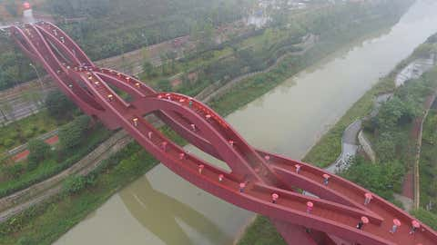 Aerial view of Chinese women displaying cheongsams on the Lucky Knot pedestrian bridge in Changsha city, central China's Hunan province, on October 23, 2016. (Imaginechina via AP Images)