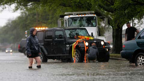 A woman whose car was stranded stands in receding street flooding, after severe rainstorms moved through New Orleans, Friday, April 1, 2016. (AP Photo/Gerald Herbert)