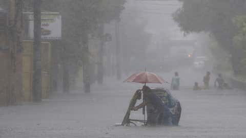 A Filipino man pushes his pedicab along a flooded road during heavy rain in suburban Mandaluyong, east of Manila, Philippines, (AP Photo/Aaron Favila)