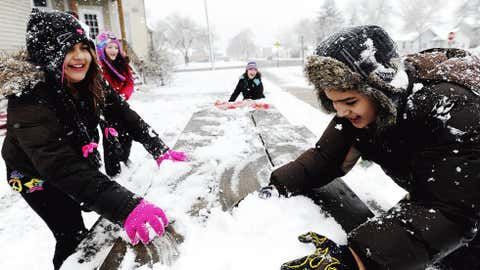 Chelsea Gerth, left, 9, and Angel Martinez Carbaja, 10, race to grab snow from a picnic table during a snowball fight in the fresh snow, Sunday, Dec. 9,, in Winona, Minn. Around three inches of snow had fallen by noon on Sunday. (AP Photo/Winona Daily News, Joe Ahlquist)