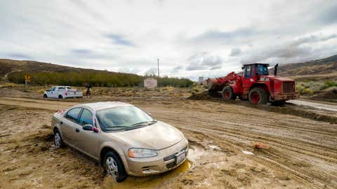 A Los Angeles County firefighter uses a front end loader to clear mud on Friday, Oct. 16, 2015, after a flash floods the day before sent mud and debris through Elizabeth Lake road in Leona Valley, Calif., trapping cars and closing roads. (AP Photo/Gus Ruelas)