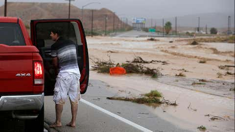 A man stands by a truck after walking through floodwaters in Moapa, Nev. Monday, Sept. 8, 2014.