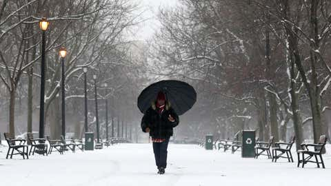 A pedestrian walks through Washington Park as light snow falls on Tuesday, Feb. 16, 2016, in Albany, N.Y. A mix of snow, sleet and freezing rain made driving conditions dicey for commuters across upstate New York, with winter storm warnings and hazardous weather advisories posted throughout the state. (AP Photo/Mike Groll)