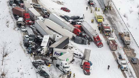 Vehicles pile up at the site of a fatal crash near Fredericksburg, Pa., Saturday, Feb. 13, 2016. The pileup left tractor-trailers, box trucks and cars tangled together across several lanes of traffic and into the snow-covered median. (James Robinson/PennLive.com via AP)