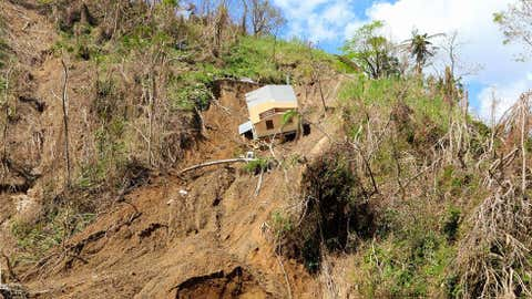 A home is shown partially swept down a hillside in the municipality of Corozal, Puerto Rico, on October 4, 2017, two weeks after Hurricane Maria ravaged the U.S. territory. Over 15 families were isolated by this landslide. (Sg. Alexis Vélez/Released-PAO)