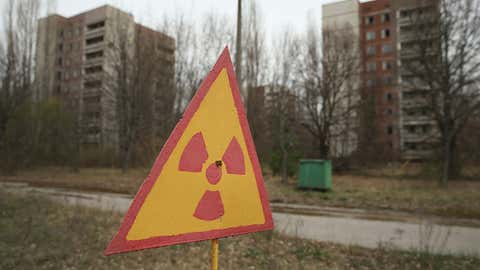 A sign warns of radiation contamination near abandoned apartment buildings on April 9, 2016 in Pripyat, Ukraine. Pripyat, built in the 1970s as a model Soviet city to house the workers and families of the Chernobyl nuclear power plant, was evacuated following the April 26, 1986 disaster, and is now a ghost town. The world is commemorating the 30th anniversary of the April 26, 1986 Chernobyl disaster.(Sean Gallup/Getty Images)