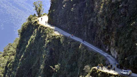 """Tourists ride their bicycles on the winding Yungas Road, one of the world's most dangerous roads, in Bolivia.  The road, which connects La Paz to Coroico, is so dangerous that is popularly known as """"Death Road.""""  (AIZAR RALDES/AFP/Getty Images)"""