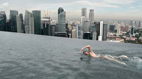 Swimming on top of the world? The Marina Bay Sands SkyPark infinity pool, designed by renowned architect, Jean-Michel Gathy of Denniston Architects, is located 57 stories above the ground. Stretching nearly 500 feet, it's one of the largest infinity pools in the world and provides stunning views of the Singapore skyline. (ROSLAN RAHMAN/AFP/Getty Images)