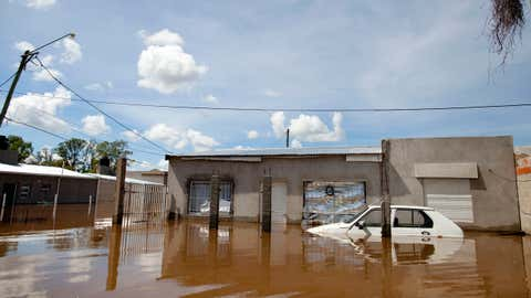 A car and homes are submerged in flood water in Concordia, Argentina, Monday, Dec. 28, 2015. At least 20,000 have been evacuated in Argentina. Neighboring Paraguay has been hardest hit, with 100,000 evacuating. Several thousand have also been evacuated in Uruguay and southern Brazil. (AP Photo/Natacha Pisarenko)