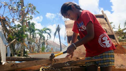 A girl helps her parents repair their storm-damaged home by removing nails from plywood on Saturday, Aug. 8, 2015, in Saipan, Northern Mariana Islands. President Barack Obama has declared the Commonwealth of the Northern Mariana Islands a disaster area and is ordering federal aid to help the U.S. territory in the aftermath of a destructive typhoon. (AP Photo/Daniel Lin)