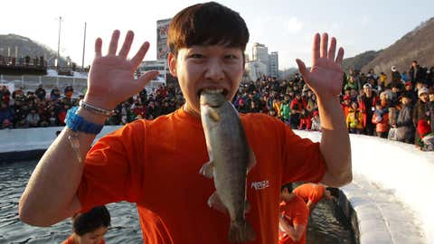 A man bites one of the fish he caught during the Hwacheon Sancheoneo (Mountain Trout) Ice Festival on January 10, 2015 in Hwacheon-gun, South Korea. The annual event attracts thousands and features a mountain trout ice fishing competition, where participants compete with traditional lures or bare hands.  (Chung Sung-Jun/Getty Images)