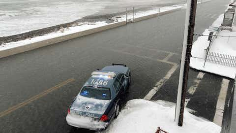 A state police cruiser parks along Winthrop Shore Drive just after high tide as side streets were flooded during a storm that left as much as a foot of snow in some areas, March 8, 2013. (Darren McCollester/Getty Images)