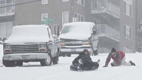 Gordon Jacobson (R) gives a push to Jaloni, 8, and father Tyrell Fincher at the top of a closed snow-covered street on January 18, 2012. (Stephen Brashear/Getty Images)