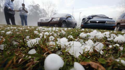Golfball-sized hail litters the ground near Andrew Stamps and his wife Valorie as they cover the shattered rear window of her 2009 Toyota Avalon in Pearl, Miss., Monday, March 18, 2013. (AP Photo/Rogelio V. Solis)
