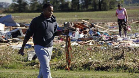 Coleman Jenkins carries some of his mother's personal items as he and friends, relatives and neighbors salvage items from the remains of Gladys Berry's mobile home in Anguilla, Miss., Thursday, Oct. 18, 2012 following a night and early morning of severe weather that destroyed several homes in this Delta community and sent some of its residents to area hospitals. (AP Photo/Rogelio V. Solis)