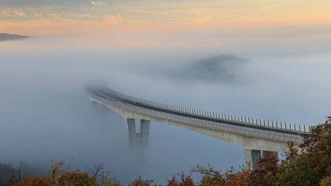 A bridge is covered in fog so thick it looks like it is rising from the clouds.  The dense fog creates an eerie atmosphere once the sun goes down and the red, green and blue lights from cars and the road's streetlamps seem to seep into the clouds. The bridge, which connects inland Slovenia with coastal areas and the Adriatic sea, was engulfed in fog for several days due to thermal inversion, where a layer of warm air lies over a layer of cooler air.  (Marko Korosec/Solent News)