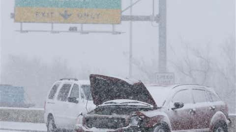 A wrecked car sits in the middle of US Highway 54 near downtown Wichita, Kan. as heavy snow falls on Wednesday morning, Feb. 20, 2013. (AP Photo/The Wichita Eagle, Travis Heying)