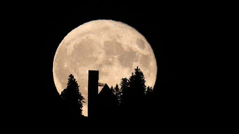 The moon is pictured on October 16, 2016 behind the St George church in Stoetten, southern Germany. (KARL-JOSEF HILDENBRAND/AFP/Getty Images)