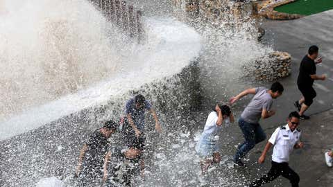 This photo taken on September 14, 2017 shows people reacting as a wave, caused by Typhoon Talim, crashes over a promenade in Wenling in China's eastern Zhejiang province. (STR/AFP/Getty Images)