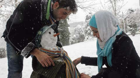 Iranians dress a snowman they made at Laleh (Tulip) park in downtown Tehran, Jan. 6, 2008.  (Photo credit:  BEHROUZ MEHRI/AFP/Getty Images)