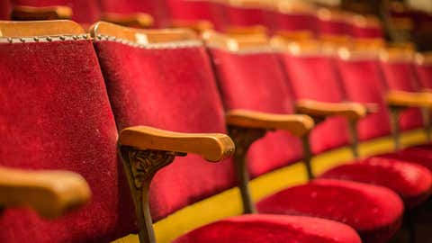 Old fashion cinema theatre seats with wooden arms and flip-up seats