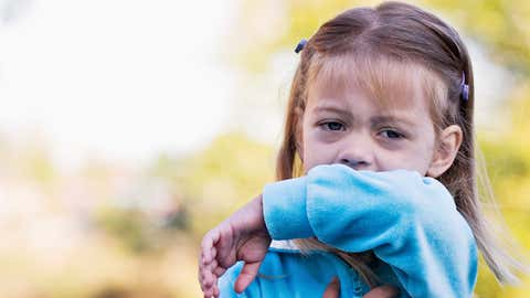 A school age girl sneezes into her arm. Her form shows the viewer the correct way to sneeze or cough, namely, by covering her mouth with the inside of her elbow and not her hands. (Credit: Thinkstock)