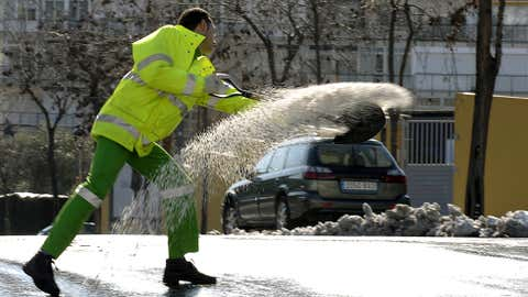 A municipal worker spreads salt on a street of Barcelona on March 9, 2010 after a heavy snowfall. Barcelona saw its heaviest snowfall since 1962, triggering emergency measures. (Lluis Gene/AFP/Getty Images)