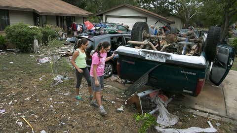 Sisters Briana Arriaga, right, and Angelina Arriaga, left, look over their father's truck that was found several houses down the block and overturned in a neighbor's front lawn in the Thoroughbred Farms subdivision near Elroy, Texas on Saturday, Oct. 31, 2015. Nearby Dry Creek overflowed, engulfing their homes and sending debris downstream. (Ralph Barrera/Austin American-Statesman - statesman.com via AP)