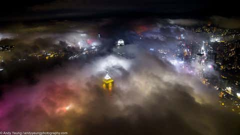 The city lights of Victoria Harbor in Hong Kong, China, create a rainbow of color in the fog.