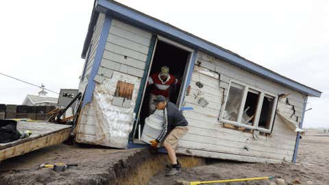 Pete Duhamed helps Christopher Hamilton remove a toilet from a cottage damaged by Hurricane Sandy at Roy Carpenter's Beach in South Kingstown.   (Greg M. Cooper/US PRESSWIRE)