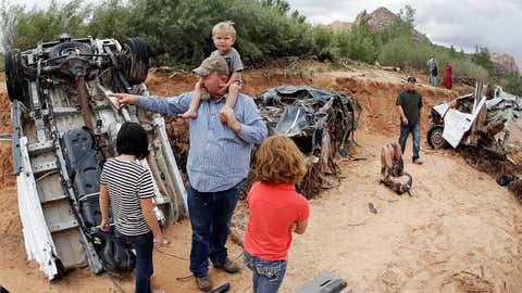 Russ Cook and his family stands next to severely damage vehicles swept away during a flash flood Tuesday, Sept. 15, 2015, in Hildale, Utah. Water swept away the vehicles in the Utah-Arizona border town, killing several people.
