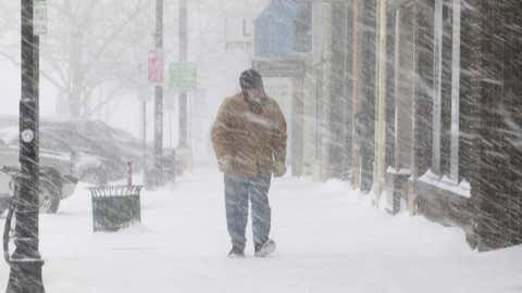 Snow and wind create poor visibility on Tuesday, April 9, 2013, as a man walks along a street in Rapid City, S.D. (AP Photo/Rapid City Journal, Chris Huber)
