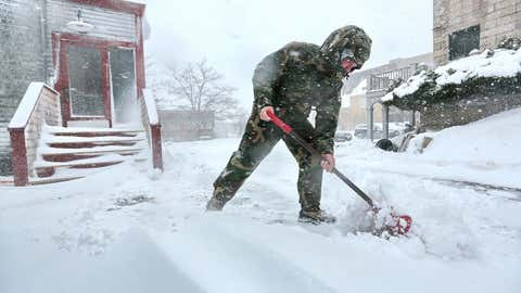 Jason Souza sweeps the snow from a driveway in New Bedford, Mass., during a snowstorm on Monday, Feb. 8, 2016.   The second winter storm in four days to hit the Northeast is expected to bring blizzard conditions to Cape Cod and southeastern Massachusetts and leave behind as much as 18 inches of snow. (Peter Pereira/Standard Times via AP)
