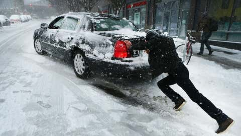 A man pushes a car stuck in the snow on February 9, 2017 in the Brooklyn borough of New York City. A major winter storm warning is forecast from Pennsylvania to Maine with the New York City area expected to receive up to one foot of snow. New York City schools are closed for the day.  (Spencer Platt/Getty Images)