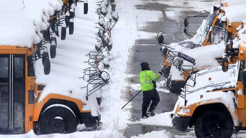 A worker clears snow off school buses, after schools were closed due to a storm, in Manchester, N.H., Monday, Feb. 13, 2017. Another winter blast of snow and strong winds moved into the Northeast on Sunday, just days after the biggest storm of the season. (AP Photo/Charles Krupa)
