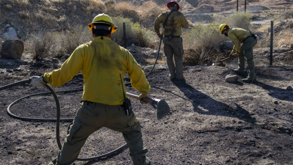 california wildfire grows in size  firefighter rescues two residents fleeing the blaze