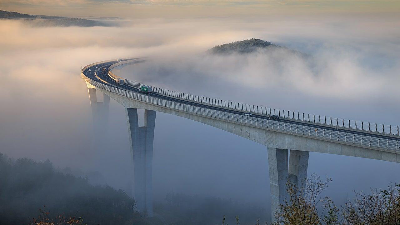 photos  bridge in slovenia seems to disappear into extreme fog