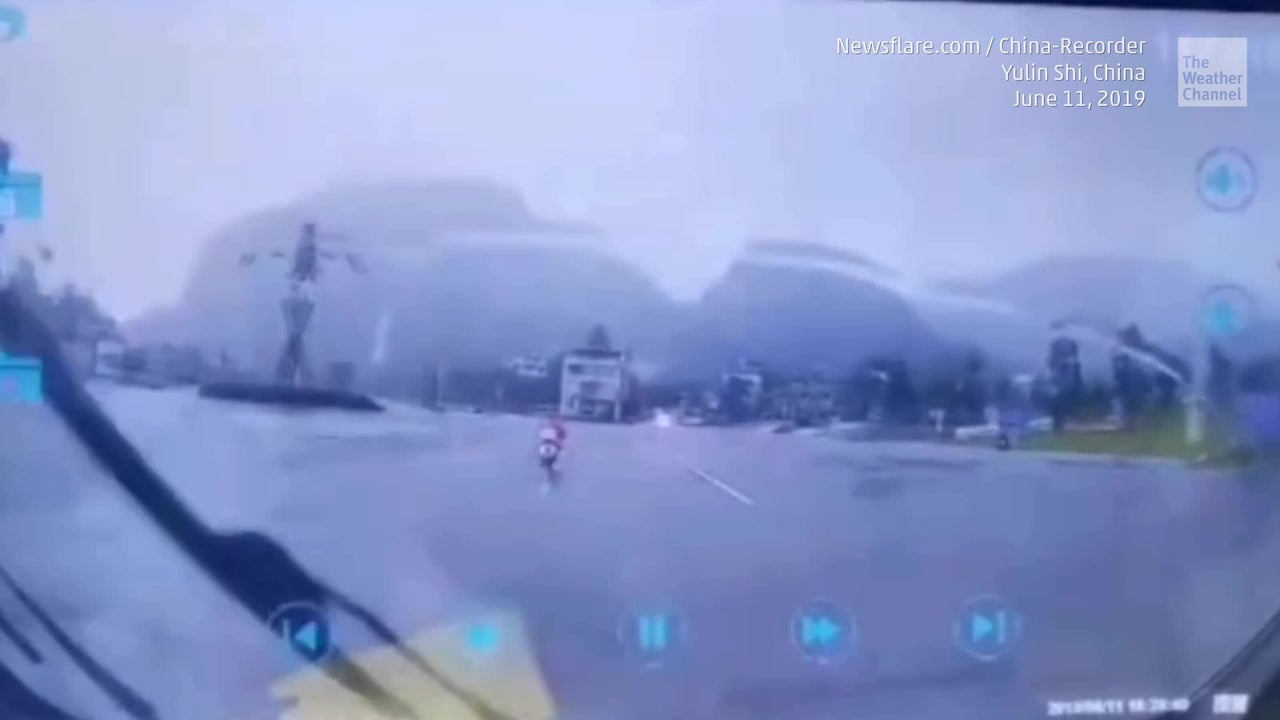Dashcam video captures the dramatic moment lightning nearly strikes a scooter driver in southern China.