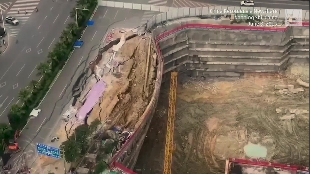 A camera captures a massive road collapsing into a construction site in southern China.