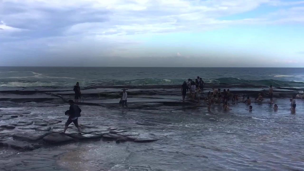Das hatten sie nicht erwartet: Plötzlich bricht eine große Welle herein und überrascht eine Gruppe von Touristen in Australien.