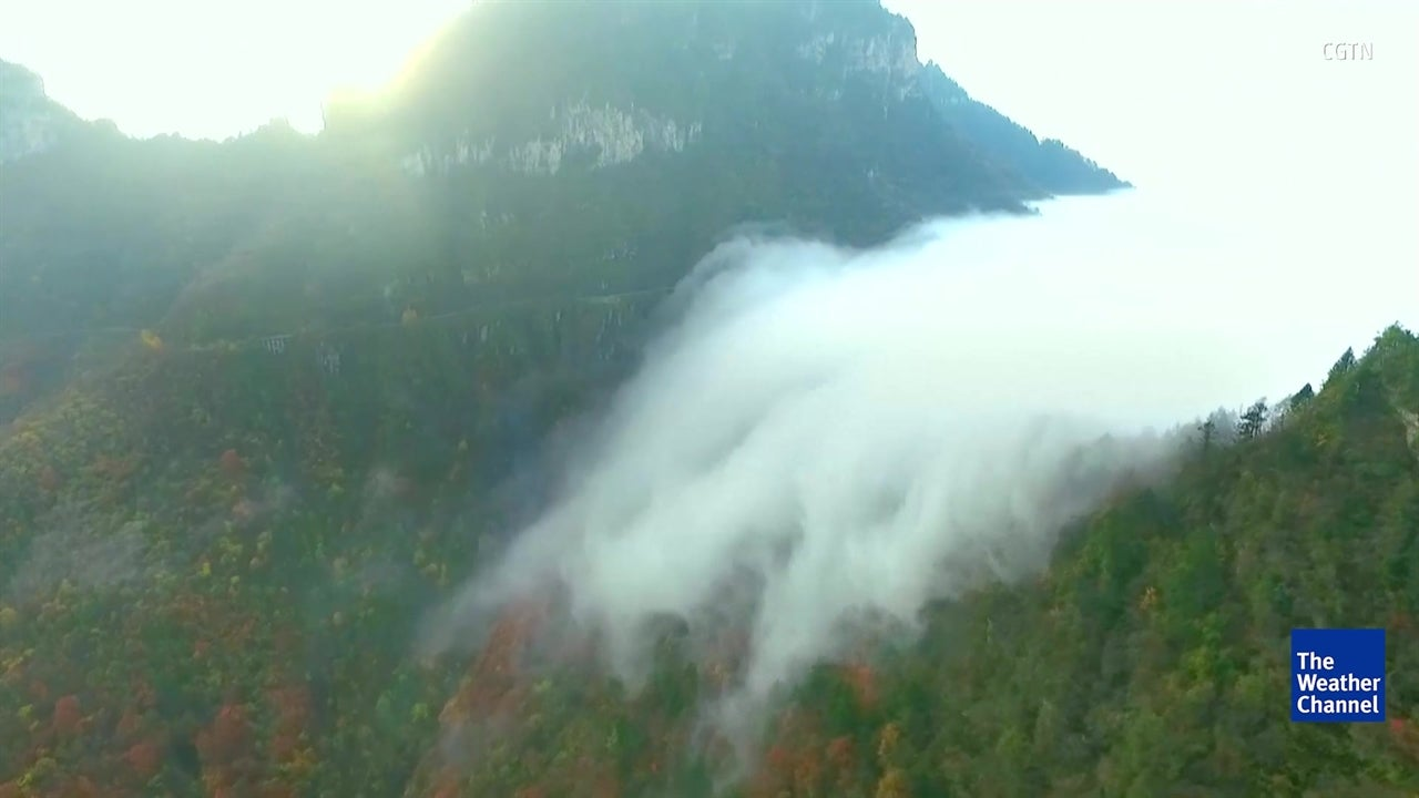 Cloud waterfall tumbles down mountainside