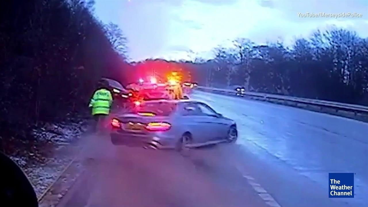 Car skids off road towards police officer
