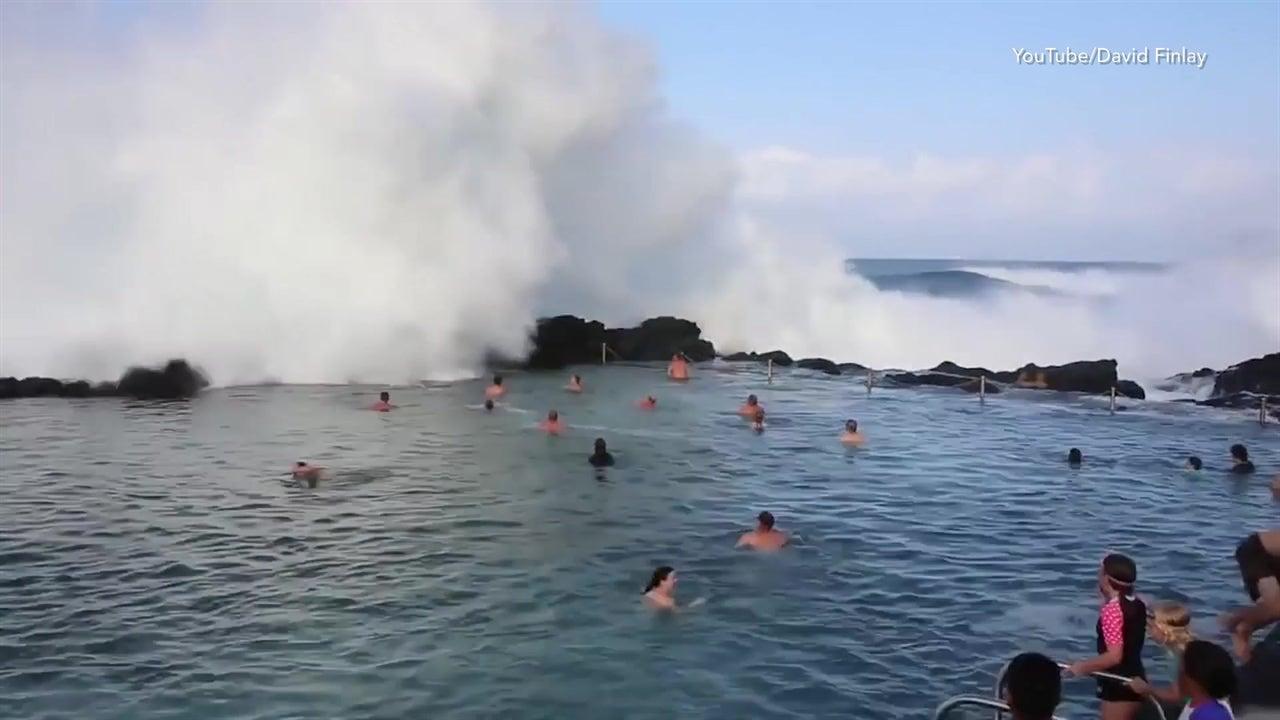 Mega waves crash over surprised swimmers