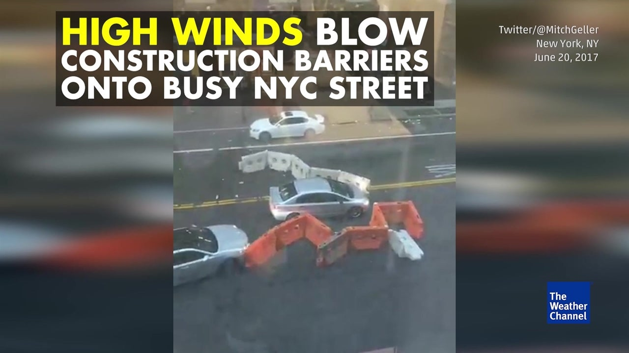 Watch: Wild winds blow construction barriers into traffic