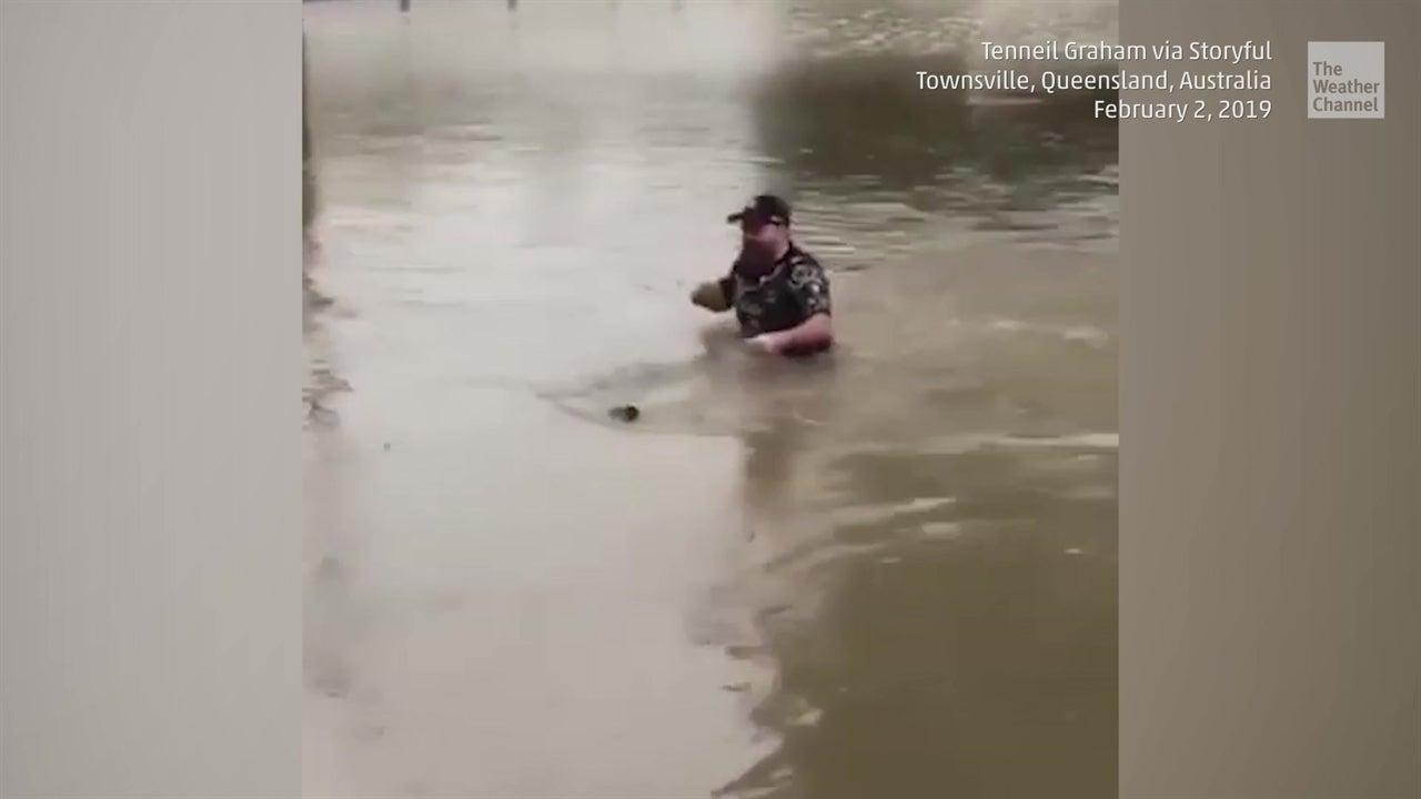Hombre checa su correo en plena inundación