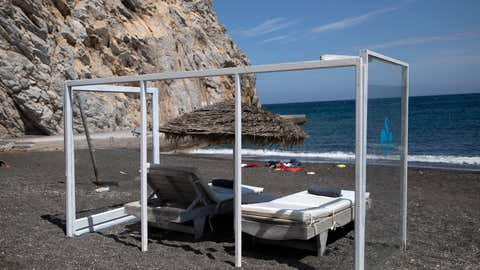 A plexiglas construction is set around an umbrella and sunbeds as a precaution against the coronavirus disease (COVID-19), on the beach of Perissa on the island of Santorini, Greece, May 7, 2020. REUTERS/Alkis Konstantinidis
